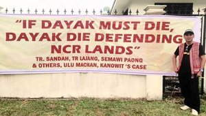 Bill Kayong with banner on indigenous land rights