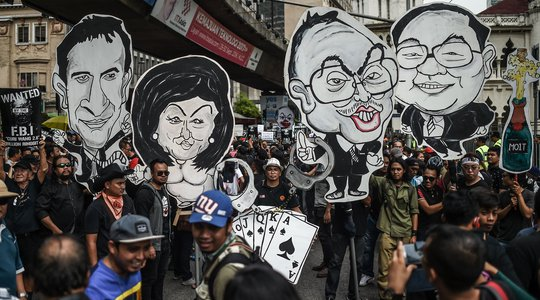 Student activists holds up clown-faced caricature of Malaysian Prime Minister Najib Razak (2nd R) and his wife Rosmah Mansor (2nd L) during a protest over a financial scandal involving state fund, 1MDB, in Kuala Lumpur on August 27, 2016.