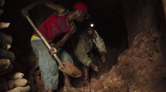 Artisanal miners dig a tunnel of a cassiterite mine