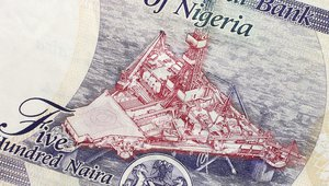 Part of Nigerian currency with oil platform
