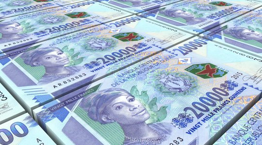 Guinean francs bills stacked background