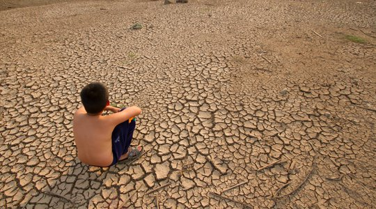 Child sits on cracked earth. Copyright: piyaset/iStockPhoto